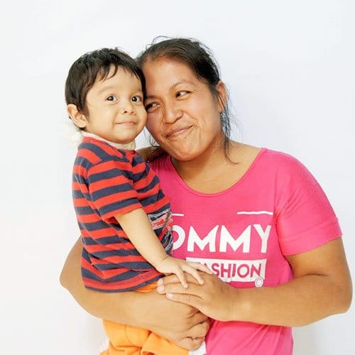 mom holding boy in striped shirt