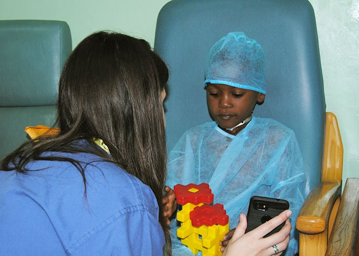 little boy waiting for surgery talking to nurse