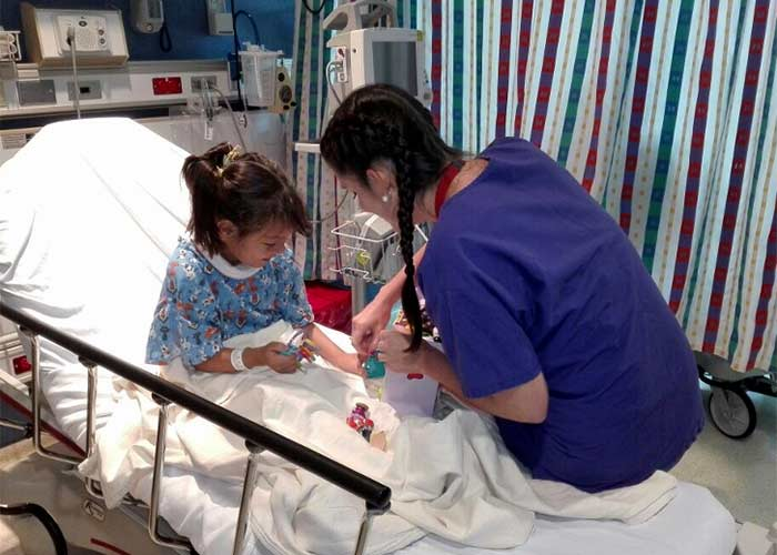 nurse working with Melanie while in hospital bed